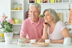 Happy senior couple sitting at kitchen table. And drinking tea with cookies Royalty Free Stock Images