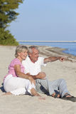 Happy Senior Couple Sitting Pointing on Beach. Happy senior men and women couple together sitting and pointing on a deserted tropical beach Royalty Free Stock Photo