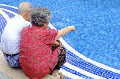 A happy senior couple sitting beside a pool Royalty Free Stock Photos