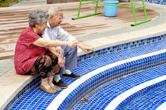 Happy senior couple sitting beside a pool. An intimate senior couple sitting beside a pool Royalty Free Stock Photography