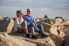 Happy senior couple sitting on rocks by the sea royalty free stock image