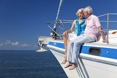 Happy Senior Couple Sitting on a Sail Boat. A happy senior couple sitting on the deck of a sail boat on a calm blue sea Royalty Free Stock Image