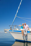 Happy Senior Couple Sitting on the Side of a Sail Boat. A happy senior couple sitting on the side of a sail boat on a calm blue sea Royalty Free Stock Photo