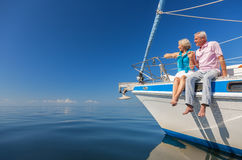 Happy Senior Couple Sitting on the Side of a Sail Boat. A happy senior couple sitting on the side of a sail boat on a calm blue sea Royalty Free Stock Photography