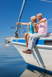Happy Senior Couple Sitting on the Side of a Sail Boat. A happy senior couple sitting on the side of a sail boat on a calm blue sea, the women is pointing to the Stock Photography