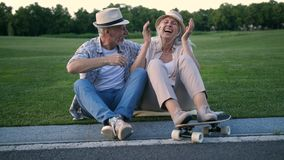 Happy senior couple laughing after skateboarding stock footage