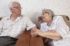 Happy Senior Couple Sitting On Sofa Royalty Free Stock Photos