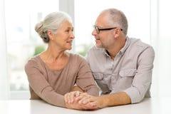 Happy senior couple sitting on sofa at home Stock Photos