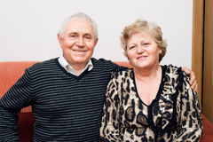 Happy senior couple sitting on the sofa at home and smiling Stock Photography