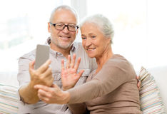 Happy senior couple with smartphone at home Stock Photo