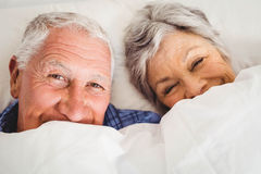 Happy senior couple smiling in bed Stock Photography