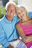 Happy Senior Couple Smiling Outside in Sunshine. Happy senior man and woman couple sitting together outside in sunshine Stock Photography