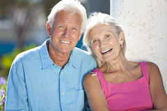 Happy Senior Couple Smiling Outside in Sunshine. Happy senior man and woman couple sitting together outside in sunshine Stock Images