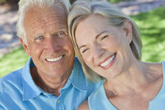Happy Senior Couple Smiling Outside in Sunshine. Happy senior men and women couple sitting together outside in sunshine stock images
