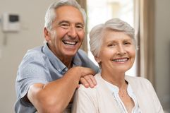 Happy senior couple smiling. Portrait of happy healthy senior couple at home. Romantic old couple sitting together on sofa while looking at camera. Cheerful stock images