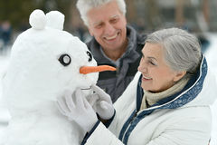 Happy senior couple with snowman Royalty Free Stock Image