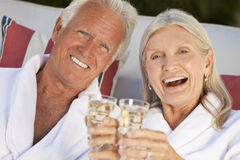 Happy Senior Couple In Spa Bathrobes & Champagne. Happy senior man and woman couple at health spa in white bathrobes smiling and drinking champagne Royalty Free Stock Photos