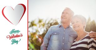 Happy senior couple standing with arm around on a sunny day. Composite image of happy senior couple standing with arm around on a sunny day royalty free stock image