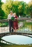 Happy senior couple standing on the bridge near river stock images