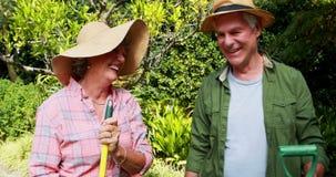 Happy senior couple standing with gardening tools 4k. Happy senior couple standing with gardening tools in garden 4k stock video