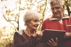 Happy senior couple standing in park and using iPod. Close up Royalty Free Stock Photos
