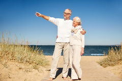 Happy senior couple on summer beach. Family, age, travel, tourism and people concept - happy senior couple pointing finger to something on summer beach Stock Photography