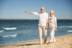 Happy senior couple on summer beach. Family, age, travel, tourism and people concept - happy senior couple walking and pointing finger to something on summer Royalty Free Stock Image