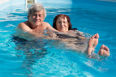 Happy senior couple in a swimming pool. Smiling senior couple enjoying time together in a swimming pool on a sunny day Stock Image