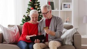 Happy senior couple with tablet pc at christmas stock footage