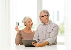 Happy senior couple with tablet pc and credit card Royalty Free Stock Images