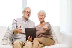 Happy senior couple with tablet pc at home Stock Photos