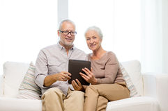 Happy senior couple with tablet pc at home Stock Images