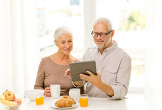 Happy senior couple with tablet pc at home Stock Photography