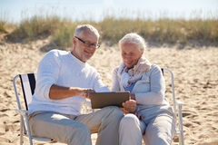 Happy senior couple with tablet pc on summer beach Royalty Free Stock Photo