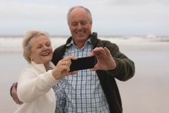 Happy senior couple taking selfie with mobile phone at the beach. Front view of active senior couple taking selfie with mobile phone standing at the beach with royalty free stock photography