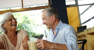 Happy senior couple talking and embracing while having coffee 4k stock footage