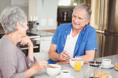 Happy senior couple talking while having breakfast Royalty Free Stock Images