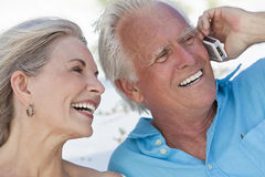 Happy Senior Couple Talking On Mobile Cell Phone Stock Images