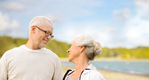 Happy senior couple talking over beach background. Old age, retirement and people concept - happy senior couple talking over beach background stock photos