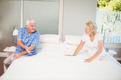 Happy senior couple talking while sitting on bed Stock Images
