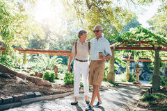 Happy senior couple talking a walk in park Stock Photo