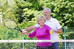 Happy senior couple at tennis court Stock Image
