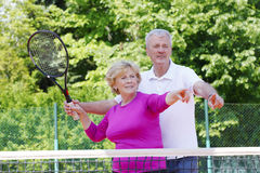 Happy senior couple at tennis court Royalty Free Stock Images