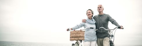 Happy senior couple with their bike. On the beach Royalty Free Stock Photo