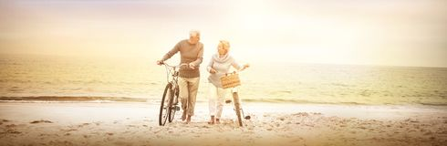 Happy senior couple with their bike. On the beach Stock Photography