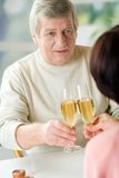 A happy senior couple toasting their years together with champag Stock Image