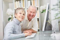 Senior couple at place of work. Happy senior couple together at place of work with computer Royalty Free Stock Photos