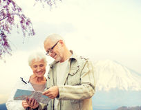 Happy senior couple with travel map over mountains Stock Photography