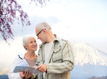 Happy senior couple with travel map over mountains Royalty Free Stock Photography