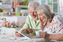 Senior couple using tablet. Happy senior couple using digital tablet in kitchen Stock Images